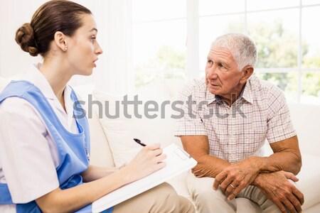 Smiling female doctor consoling senior man at table Stock photo © wavebreak_media