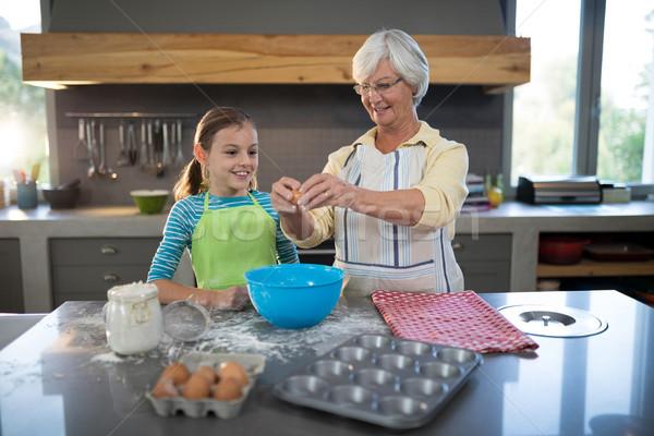 Smiling grandmother showing granddaughter to break eggs Stock photo © wavebreak_media