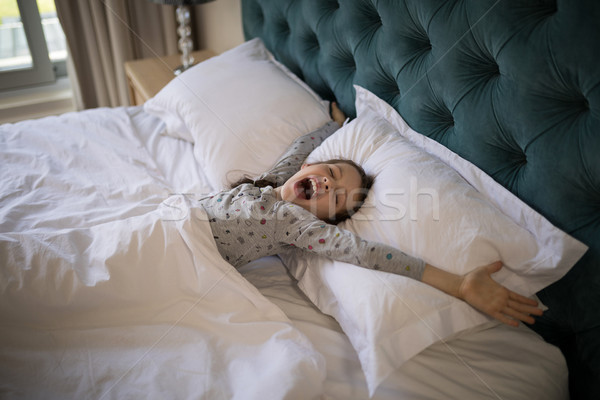 Girl yawning while stretching her arms in bed Stock photo © wavebreak_media