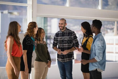 Adult student sitting on chair with friends discussing in background Stock photo © wavebreak_media