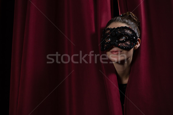 Smiling female artist in mask peeking through the red curtain Stock photo © wavebreak_media