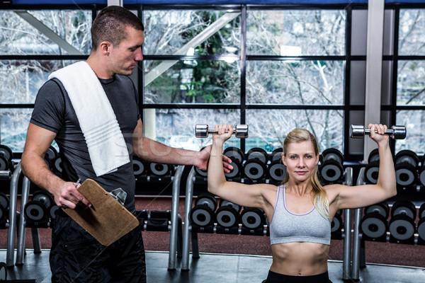 Dopasować kobieta hantle wykonywania trener siłowni Zdjęcia stock © wavebreak_media