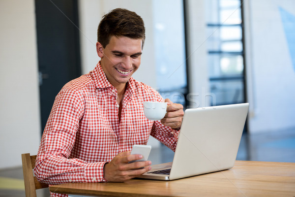 Man text messaging on mobile while having cup of coffee Stock photo © wavebreak_media