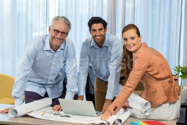 Stock photo: Businesswoman and coworker with blueprint on the desk