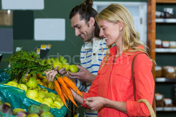 Happy couple selecting fruits and carrots in organic section Stock photo © wavebreak_media