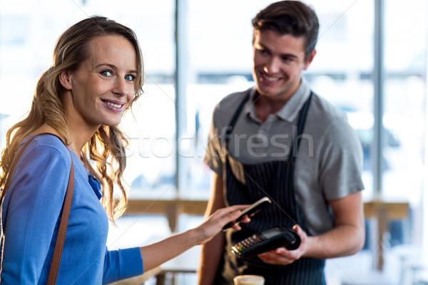 Woman paying bill through smartphone using NFC technology Stock photo © wavebreak_media