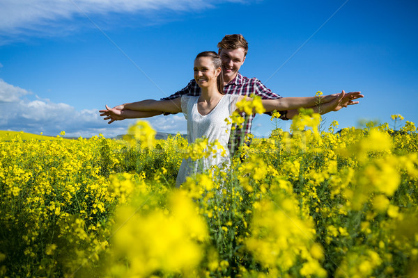 Romantic couple standing with arms outstretched in mustard field Stock photo © wavebreak_media