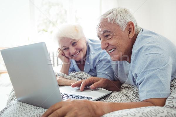 Met behulp van laptop slaapkamer computer man gelukkig Stockfoto © wavebreak_media