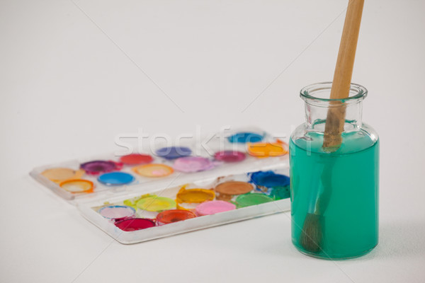 Watercolor palette and paintbrush with blue paint dipped into a jar filled with water Stock photo © wavebreak_media