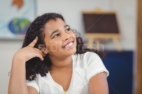 Cute pupil daydreaming in a classroom Stock photo © wavebreak_media