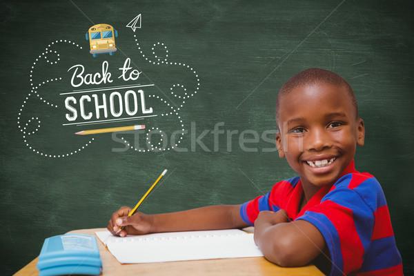 Composite image of happy pupil at desk Stock photo © wavebreak_media