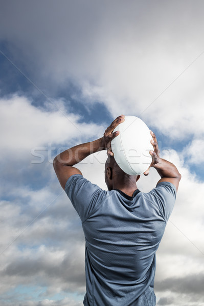 Stock photo: Composite image of rear view of sportsman throwing rugby ball