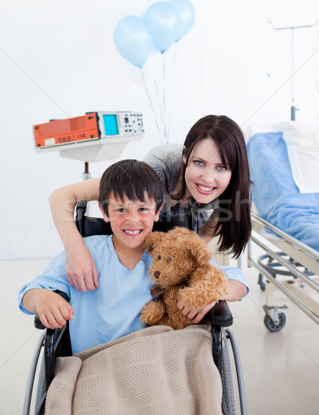 Smiling little boy sitting on wheelchair and his mother Stock photo © wavebreak_media