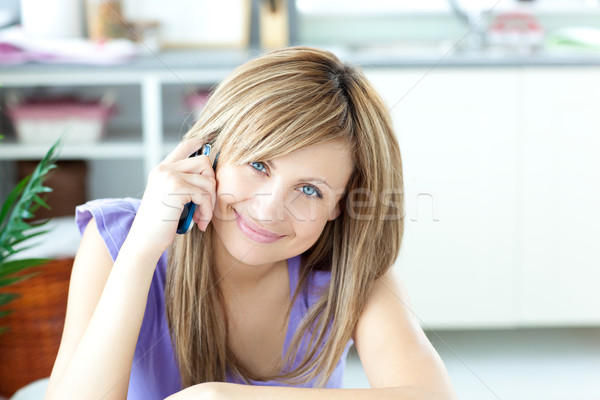 Portrait of a cheerful woman using a phone in the kitchen Stock photo © wavebreak_media