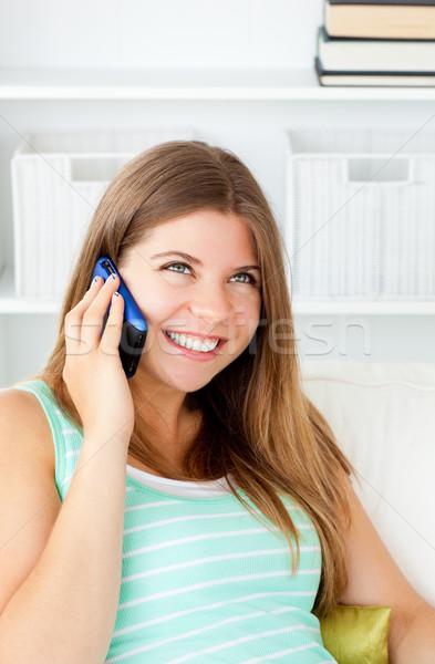 Glowing woman talking on phone sitting on a sofa at home Stock photo © wavebreak_media