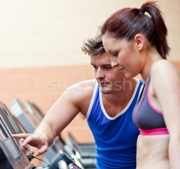 Pretty athletic woman standing on a running machine with her personal coach in a fitness center Stock photo © wavebreak_media