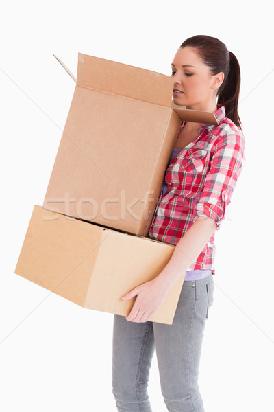 Beautiful woman looking inside a cardboard box while standing against a white background Stock photo © wavebreak_media