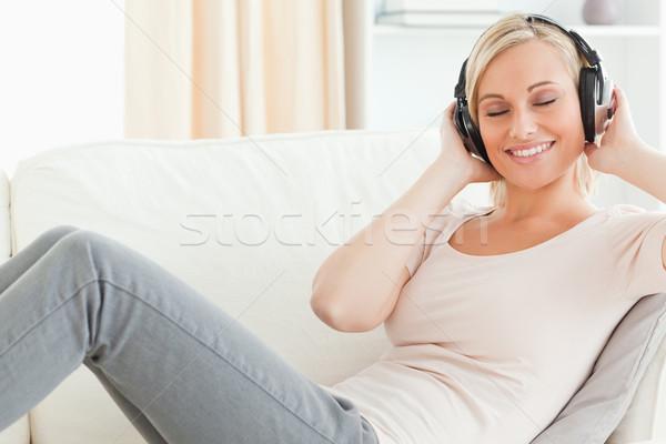 Serein femme écouter de la musique salon sourire heureux Photo stock © wavebreak_media