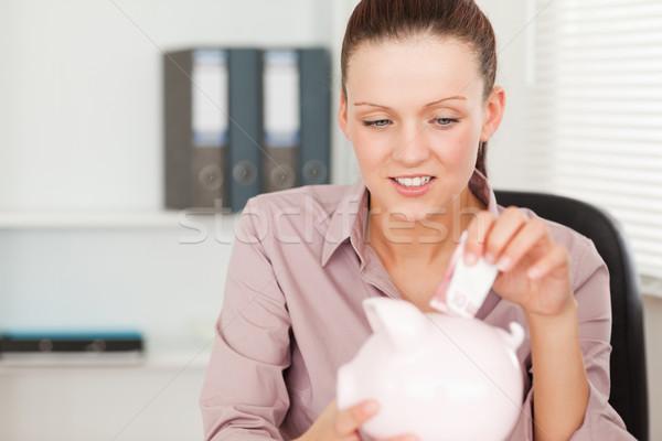 A female putting money into her piggy bank Stock photo © wavebreak_media