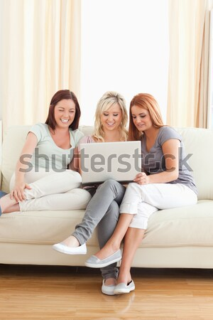 Young women lounging on a sofa watching a movie in a living room Stock photo © wavebreak_media