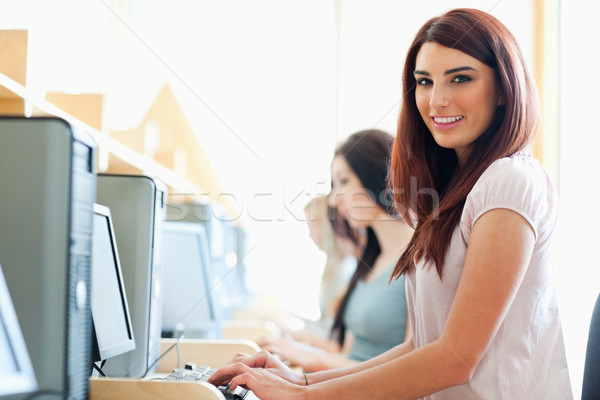 Smiling student using a computer in an IT room Stock photo © wavebreak_media