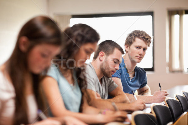 Students listening a lecturer with the camera focus on the foreground in an amphitheater Stock photo © wavebreak_media