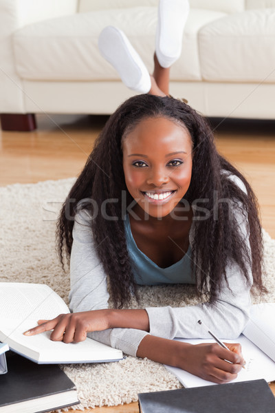 Smiling woman lying on carpet in living room doing a book review Stock photo © wavebreak_media