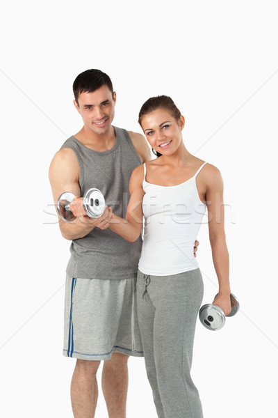 Portrait of a man helping a gorgeous woman to work out against a white background Stock photo © wavebreak_media