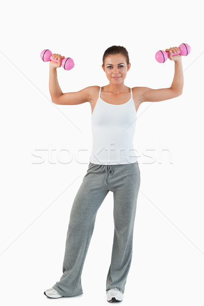 Portrait of a young woman working out with dumbbells against a white background Stock photo © wavebreak_media