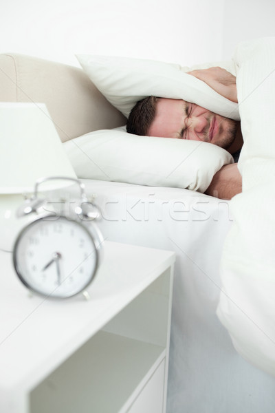 Portrait of a young man covering his ears with a pillow while his alarm clock in ringing Stock photo © wavebreak_media