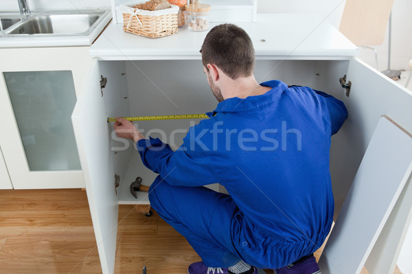 Stock photo: Repair man measuring something in a kitchen