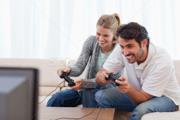 Stock photo: Cheerful couple playing video games in their living room