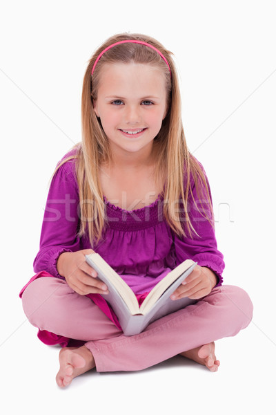 Portrait of a happy girl reading a book against a white background Stock photo © wavebreak_media