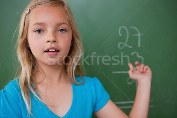 Little schoolgirl showing her result on a blackboard Stock photo © wavebreak_media