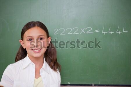 Smiling schoolboy writing an addition on a chalkboard Stock photo © wavebreak_media