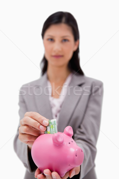 Money being put into piggy bank by businesswoman against a white background Stock photo © wavebreak_media