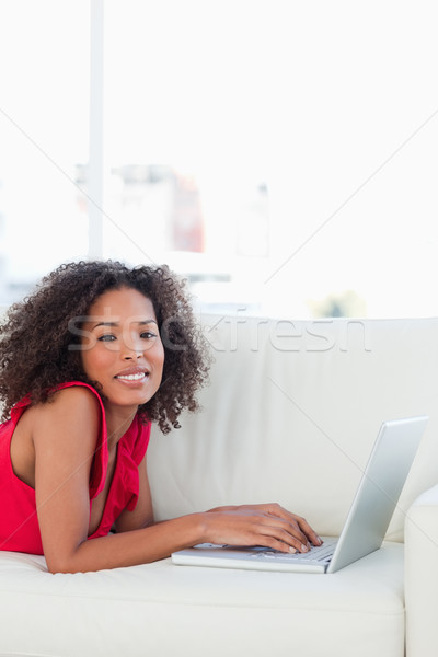 A woman using her laptop on the couch as she looks straight ahead and smiles Stock photo © wavebreak_media