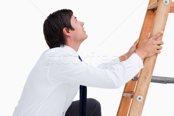 Side view of young tradesman climbing on a ladder against a white background Stock photo © wavebreak_media