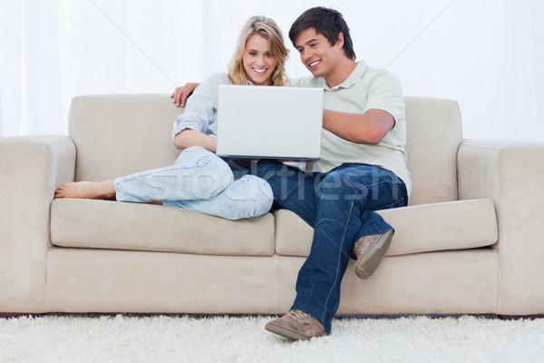 Sorridente sessão juntos sofá olhando Foto stock © wavebreak_media