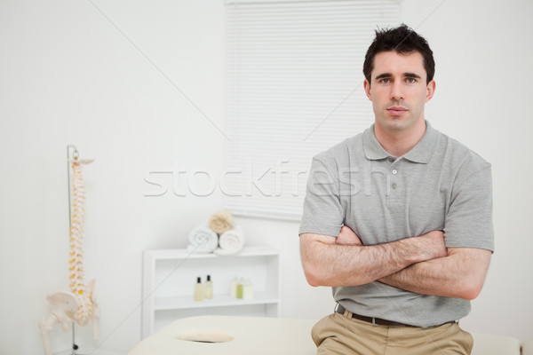 Serious physiotherapist crossing his arms in a medical room Stock photo © wavebreak_media