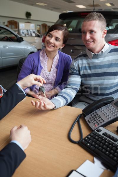 Happy couple receiving keys from a salesman in a car shop Stock photo © wavebreak_media