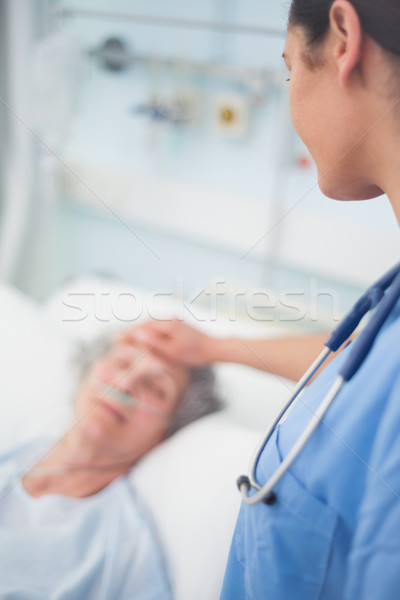 Nurse looking at a patient while touching her in hospital ward Stock photo © wavebreak_media