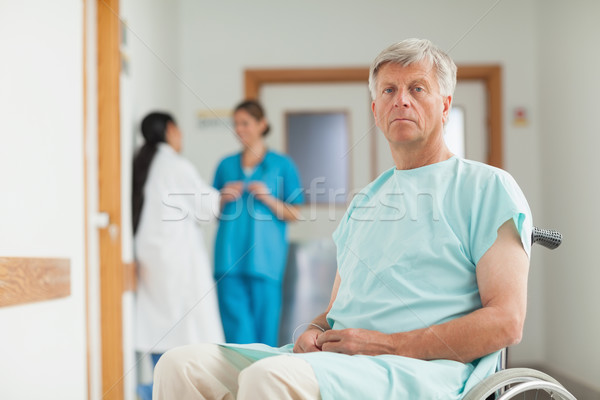 Male patient in a wheelchair looking at camera in hospital corridor Stock photo © wavebreak_media