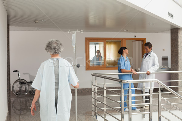 Old woman walking along the hallway in a hospital with a drip in her hand Stock photo © wavebreak_media