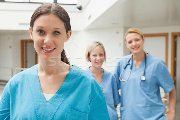 Smiling nurse with two nurse friends in hospital corridor Stock photo © wavebreak_media