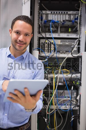 Technicians smiling while standing in front of servers in data center Stock photo © wavebreak_media