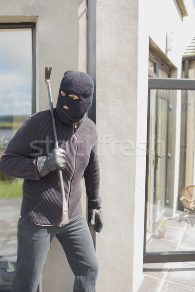 Burglar hiding behind wall with crow bar in back garden Stock photo © wavebreak_media