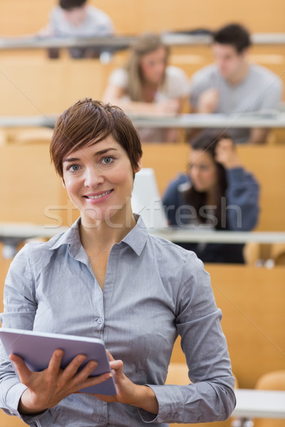 Woman standing holding a tablet computer smiling at the lecture hall  Stock photo © wavebreak_media
