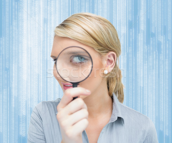 Blonde woman looking through magnifying glass Stock photo © wavebreak_media
