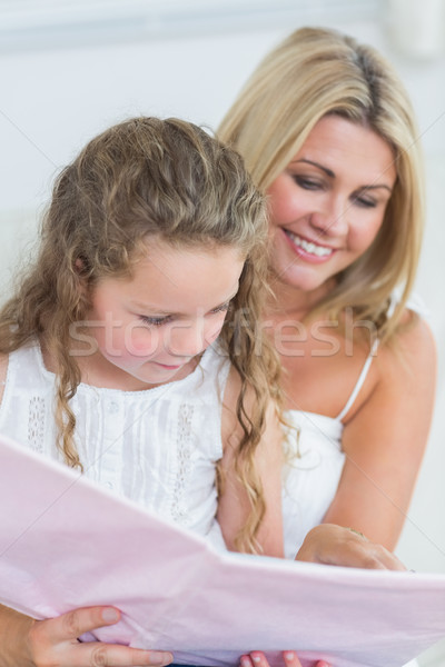 Smiling mother and daughter reading storybook together Stock photo © wavebreak_media